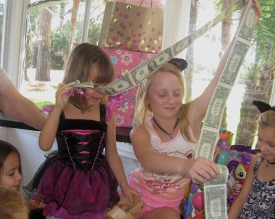 """Sophie was thrilled to get a little chest full of one dollar bills from Gigi. She said, """"Gigi, you always give me my favorite gift""""."""